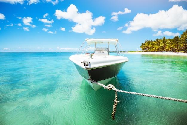 Потрясающий вид на тропический пляж с белой яхтой на пирсе