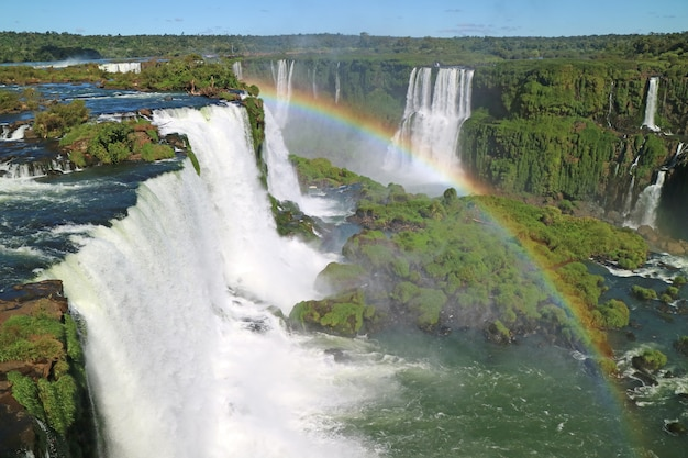 Stunning view of powerful iguazu falls  from brazilian side with a gorgeous rainbow