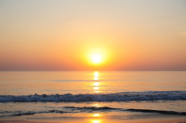 Stunning view of the sea in the rays of setting sun, reddish sunlight reflected in the water. beautiful sunset over the ocean, deserted beach, copy space