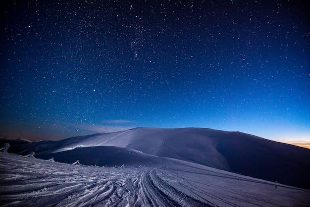 별이 빛나는 하늘을 배경으로 밤에 산의 눈 덮인 산 스키 슬로프의 멋진 전망