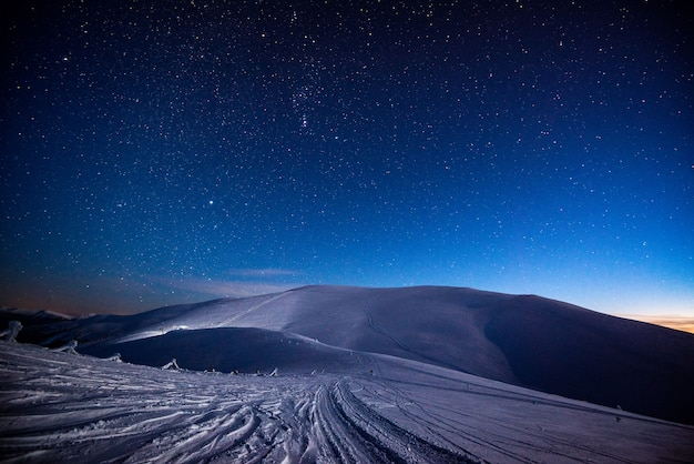 Stunning views of the snowy mountain ski slopes in the mountains at night against a starry sky