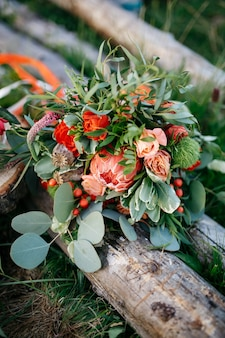 Stunning wedding bouquet made of red flowers and greenery lies o