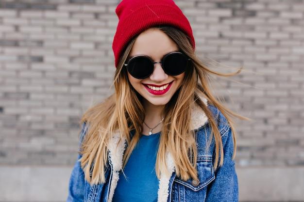 レンガの壁に分離されたスタイリッシュなデニムジャケットの見事な白人の女の子。笑顔で。黒のサングラスでエレガントな笑う女性の屋外写真。