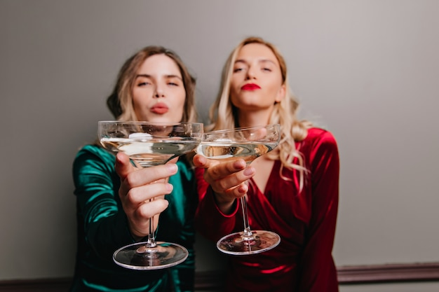 어두운 벽에 와인 잔을 올리는 멋진 백인 소녀. 와인과 함께 뭔가를 축하하는 재미있는 여성 모델.