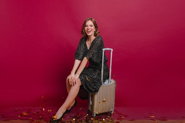 Splendida donna bianca che si siede sulla valigia con l'espressione del viso eccitato e guardando alla telecamera