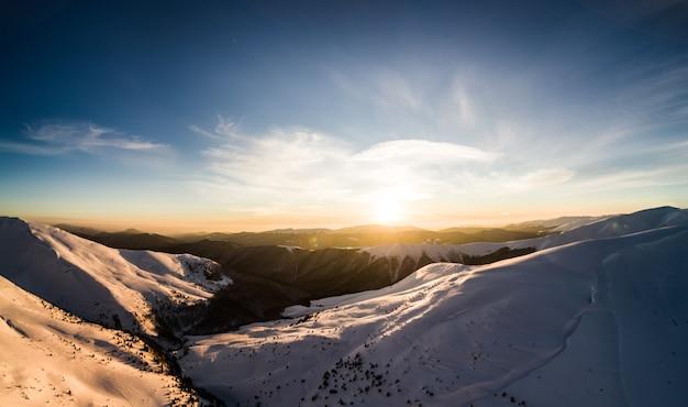 晴れた冬の凍るような日にスキーリゾートの見事な冬の山のパノラマ