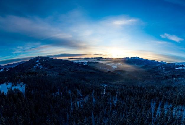 晴れた凍るような日に雪に覆われた木々や丘のある見事な冬のパノラマ