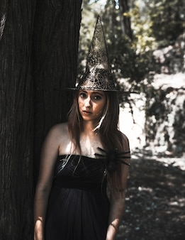 Stunning witch with creepy spider in sunny forest