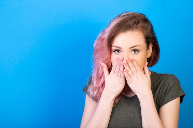 Stunning woman coquettishly covers her mouth with hands