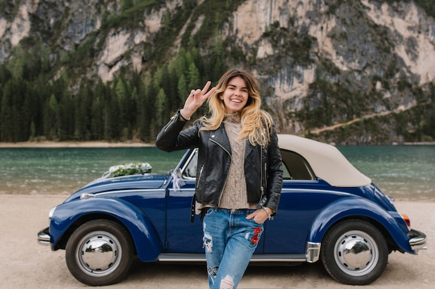 Stunning woman in denim pants and knitted jersey gladly posing beside blue car during trip around italy