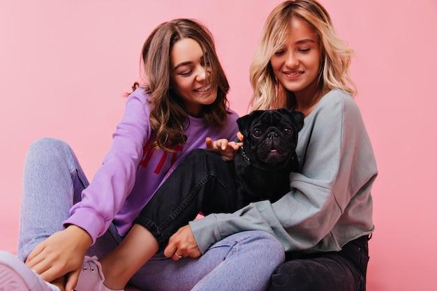 Donna sbalorditiva che tiene cucciolo nero con un sorriso affascinante. tiro al coperto di adorabili sorelle che esprimono felicità durante il servizio di ritratti con il piccolo bulldog.
