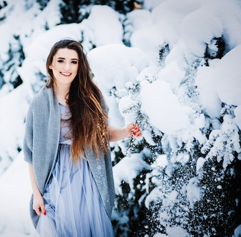 Stunning woman in a sweater and light dress stands in the garden among bushes