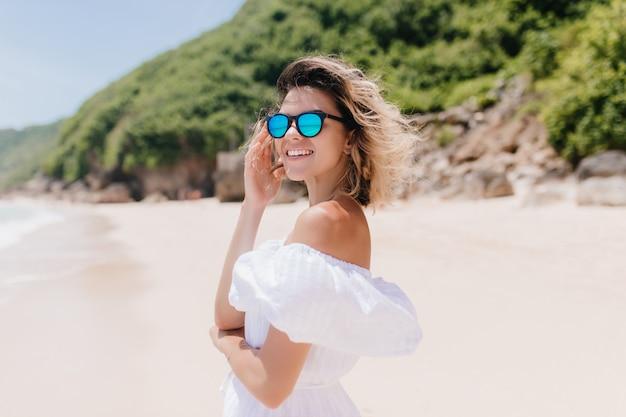 Потрясающая женщина в хорошем настроении позирует на пляже с лесом. напольное фото изысканной кавказской женской модели охлаждает на экзотическом курорте.