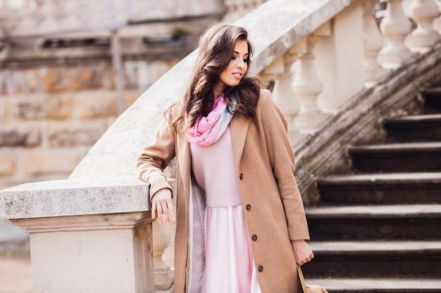 La donna sbalorditiva posa in cappotto beige sulle grandi scale di pietra