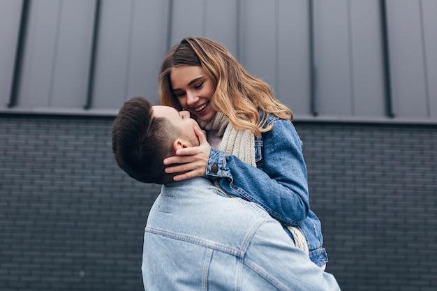 彼氏の顔に触れて彼の目を覗き込む見事な女性。夫との写真撮影中に愛を表現する感情的な若い女性の屋外写真。