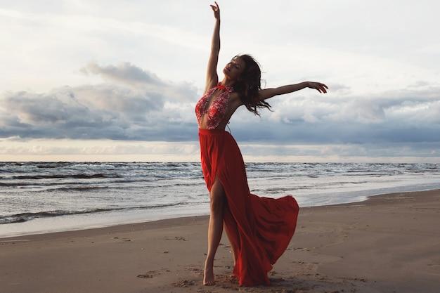 日没時にビーチで美しい赤いドレスを着ている見事な女性
