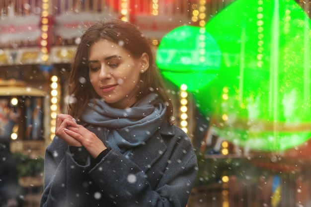 降雪時に通りを歩いている見事な女性は灰色のコートを着ています。空きスペース