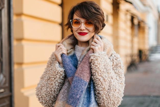 거리에 포즈를 취하는 스카프로 멋진 여자