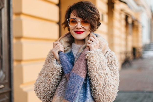Splendida donna con sciarpa in posa sulla strada