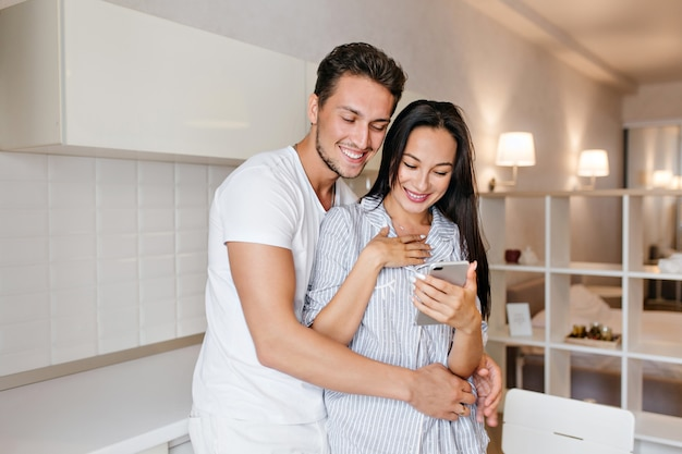 Stunning woman with surprised smile reading phone message while husband embracing her