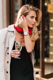 グラスワインを持ち、ブロンドの髪に触れるトレンディなメイクの見事な女性。シャンパンのゴブレットと華やかな女性モデルの屋外の肖像画。