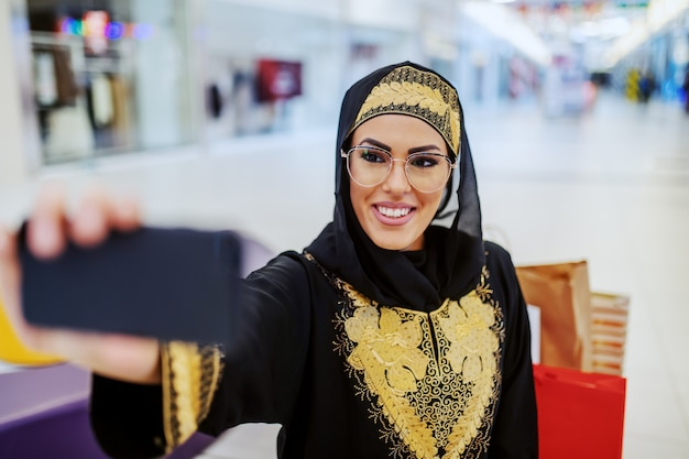 Stunning young arab woman in traditional wear with beautiful toothy smile standing in shopping mall and taking selfie for social media. millennial generation.