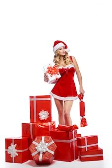 Сногсшибательная молодая женщина, одетая в рождественский наряд, позирует seducti