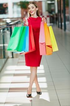 Потрясающая молодая девушка со светло-каштановыми волосами и красными губами, стоящая с красочными сумками для покупок, концепция покупок, портрет, копией пространства, счастливые эмоции.