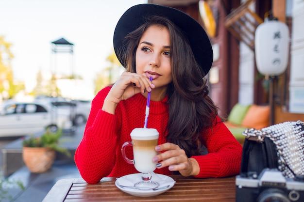 세련 된 검은 모자와 열린 공간 카페와 우유 또는 카푸치노와 음료 커피에 앉아 밝은 빨간 스웨터에 멋진 아가씨.