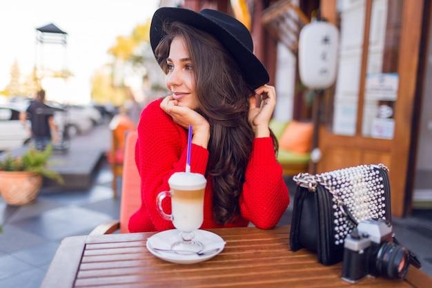 Сногсшибательная барышня в стильной черной шляпе и ярко-красном свитере сидит в открытом пространстве кафе и пьет кофе с молоком или капучино.