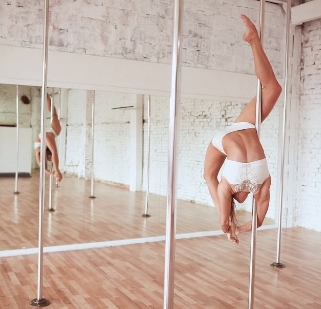 Stunning young slim woman in white clothes performs pole dance