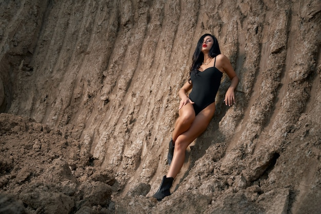 Stunning young woman in black bodysuit with slender long legs standing among sand quarry. sexy lady with bright makeup and long dark hair posing on camera outdoors.