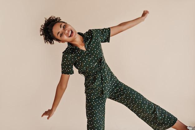 ベージュの壁で踊る見事な若い女性