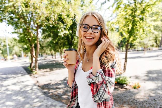 自然に一杯のコーヒーを保持しているメガネの見事な若い女性。夏の日に公園を歩いて笑顔のブロンドの女の子。