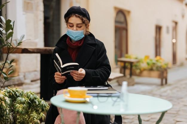 カフェのテーブルに座って、屋外で本を読んでいる医療衛生マスクの見事な若い女性。コロナウイルスの発生の予防。