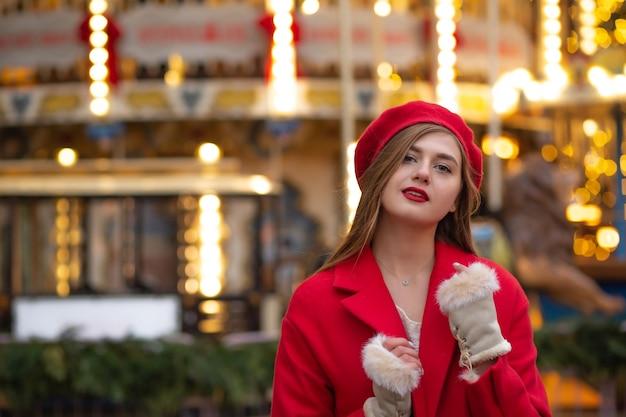 ストリートフェアを歩いている赤いコートを着た見事な若い女性。空きスペース