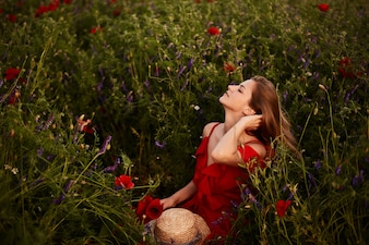 Stunning young woman in red dress sits on the green field with red poppies