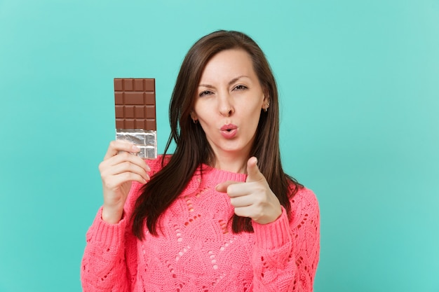 Stunning young woman in knitted pink sweater pointing index finger on camera hold in hand chocolate bar isolated on blue wall background, studio portrait. people lifestyle concept. mock up copy space.