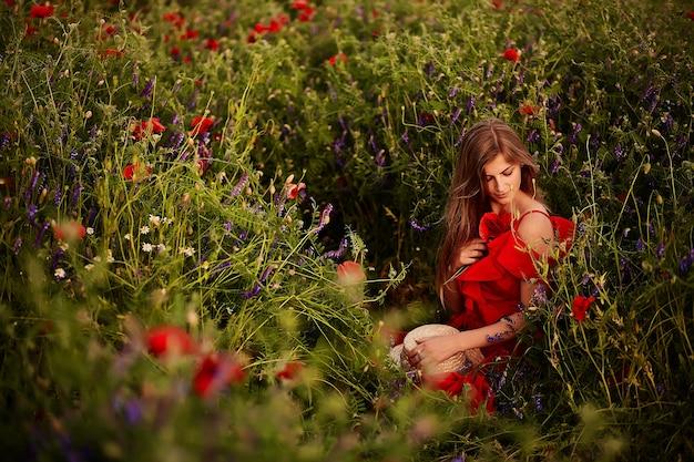 La giovane donna sbalorditiva in vestito rosso si siede sul campo verde con i papaveri rossi