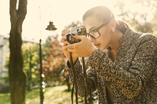 La giovane donna sbalorditiva sta con una macchina fotografica in un parco soleggiato
