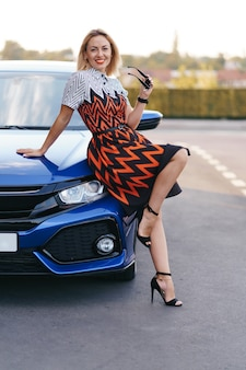 Stunning young woman waring dress posing in front of her car outdoors, ownership driver