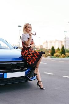 Потрясающая молодая женщина в воинственном платье позирует перед своей машиной на открытом воздухе, водитель-владелец