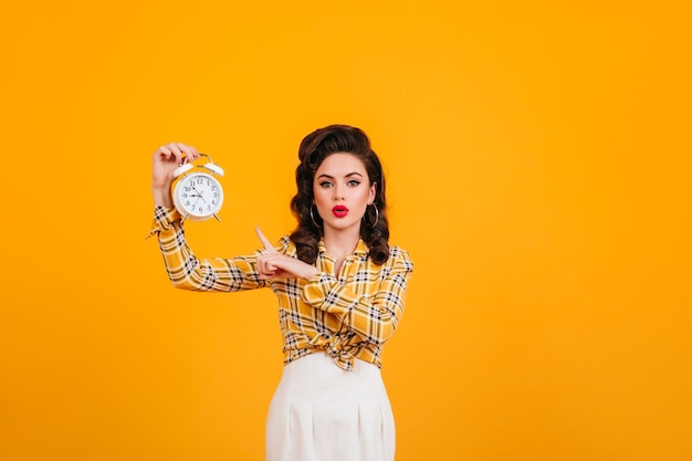 Stunning young woman with bright makeup posing with clock. studio shot of appealing pinup girl isolated on yellow background.
