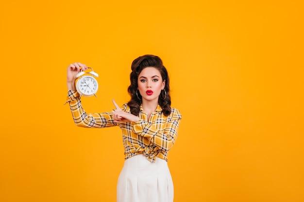 시계와 함께 포즈를 취하는 밝은 화장과 멋진 젊은 여자. 노란색 배경에 고립 된 매력적인 핀 업 소녀의 스튜디오 샷.