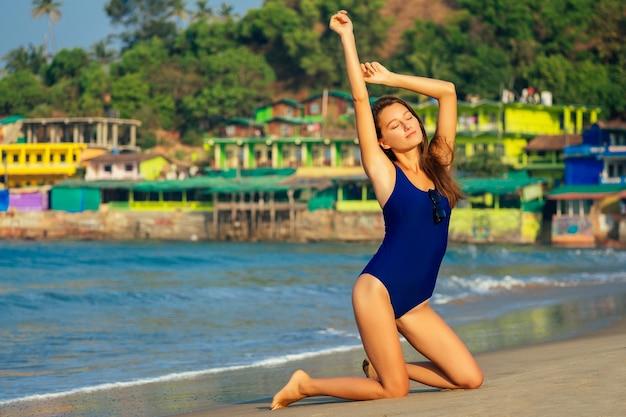 Потрясающе красивая молодая женщина позирует в купальнике и загорает на пляже. концепция детоксикации, диеты и фитнеса