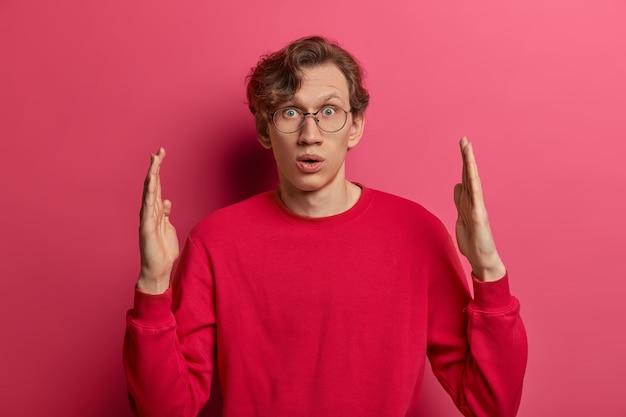Un giovane uomo stupito e stupito forma un oggetto enorme, fa qualcosa di grande, sussulta per la meraviglia, ha un'espressione sorpresa, misura e spiega le dimensioni, vestito con disinvoltura, posa contro il muro rosa