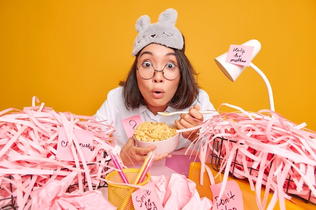 Stupefied asian woman in domestic wear has breakfast at workplace eats cornflakes cannot believe her eyes sits at desktop with cut paper around isolated over yellow wall works from home