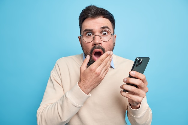 Stupefied bearded adult european man keeps mouth opened stares terrified, holds mobile phone finds out shocking news dressed in casual jumper