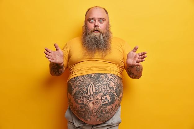 髭を生やした感情的な男は、戸惑いとショックで手のひらを広げ、表情を混乱させ、黄色に分離された驚くべきニュースに感銘を受けた小さめのtシャツから刺青の腹が突き出ています