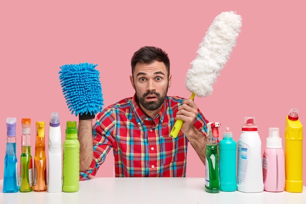 Stupefied bearded man holds brush for dust, mop, stares , cares about sanitary at home